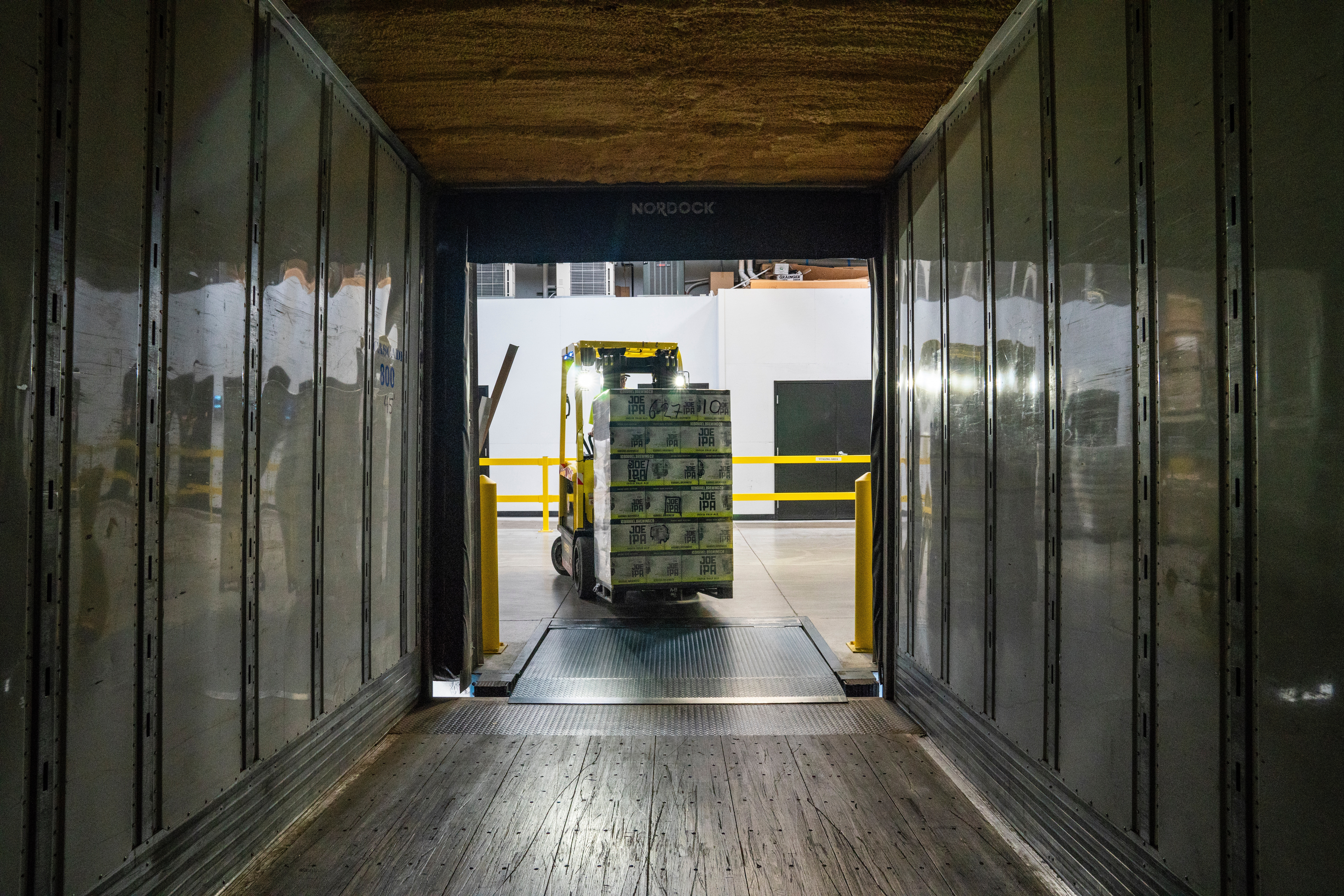 Forklift with boxes stacked driving into storage container