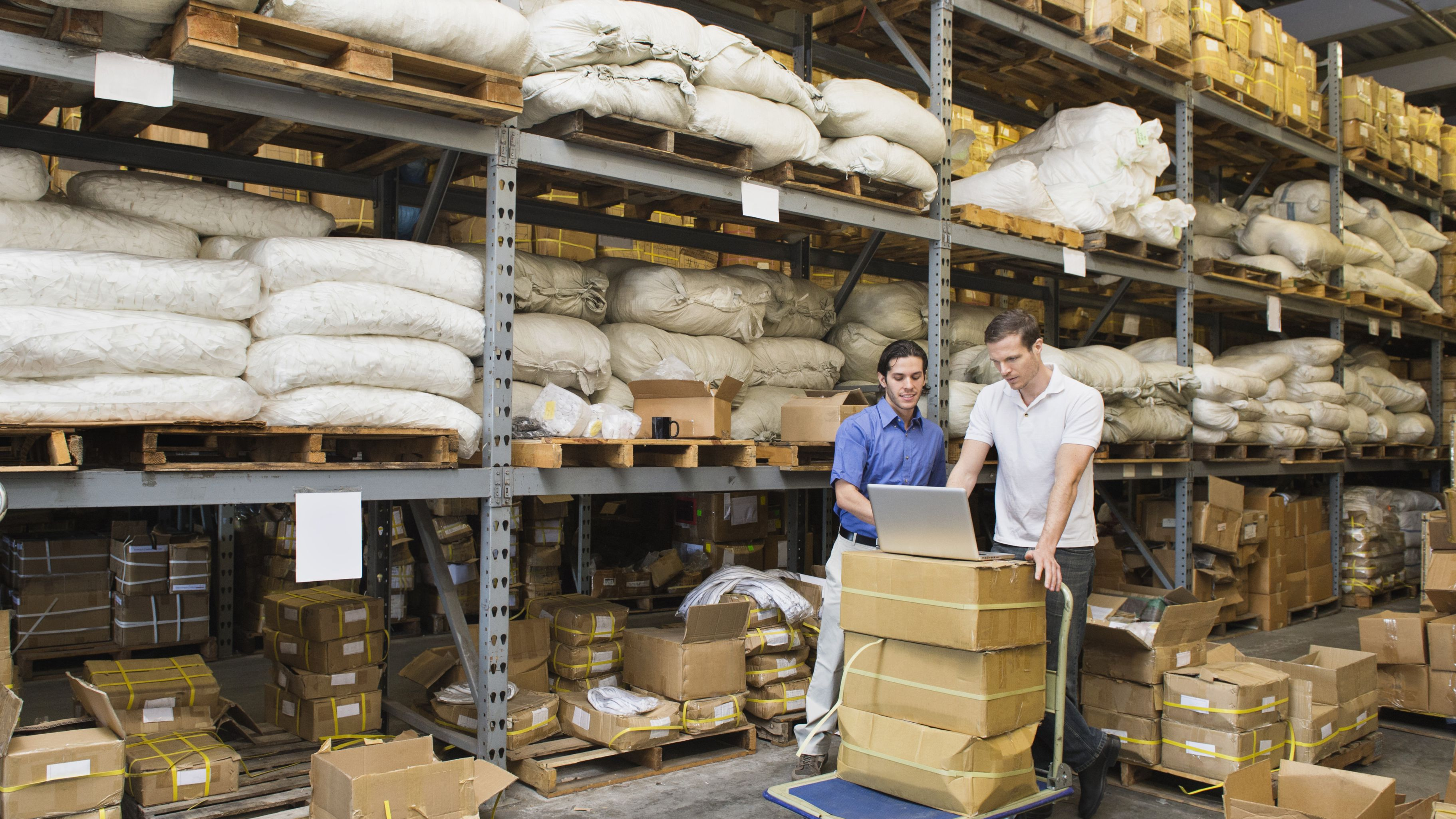 two men in warehouse with stock and laptop