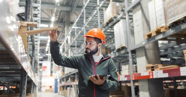 Man in a warehouse inspecting a box