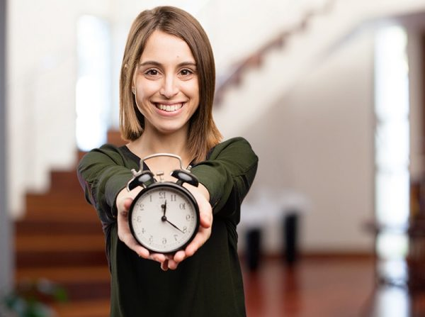 a woman smiling while holding an alarm clock