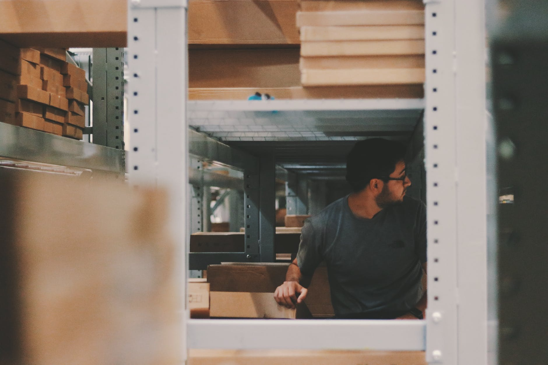Man in warehouse shelves stocking with inventory