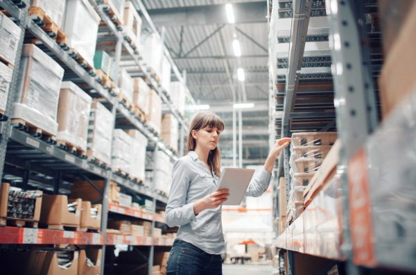 a woman doing an inventory check in a pallet warehouse