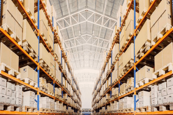 cardboard boxes stacked in pallet racks inside a warehouse