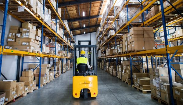 a man driving a forklift while he manages inventory in a warehouse