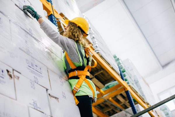 young industrial high climber woman working and checking boxes in shipping manufacturing facility warehouse