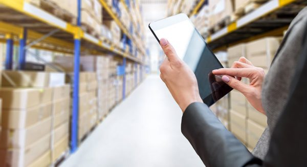 hands holding a tablet inside a warehouse