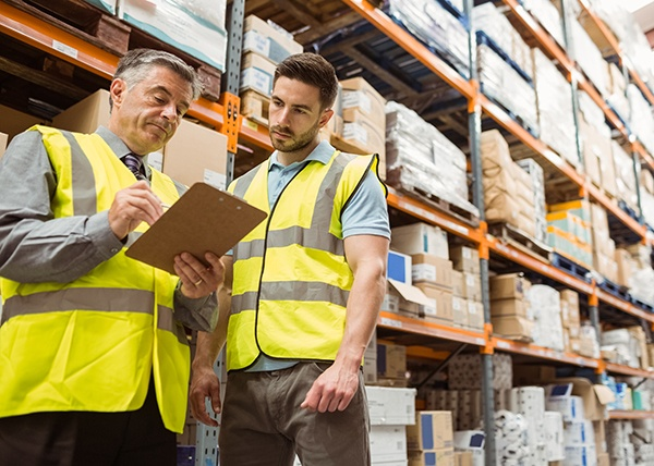 a senior team leader in a warehouse talking to a worker