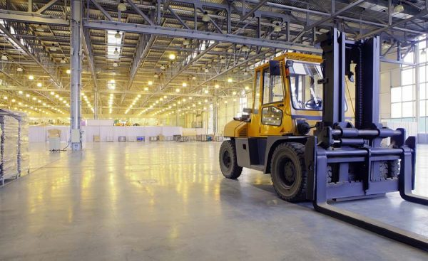 a yellow fork lift parked inside a warehouse