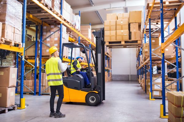 Warehouse workers stacking cardboard boxes on a pallet rack using a fork lift