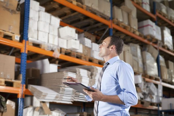 A warehouse manager checking the top shelf inventory while holding a clipboard