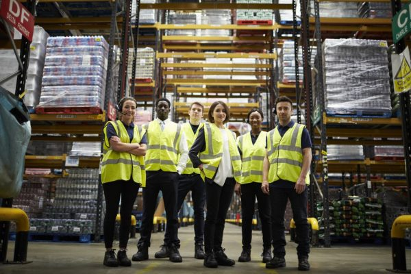 A team of warehouse workers standing inside a warehouse