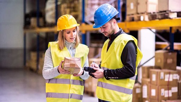 Two warehouse workers checking a package
