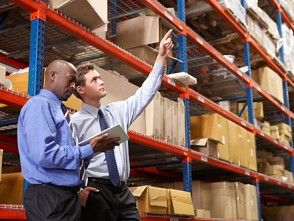 Two business men doing an inventory check in a warehouse